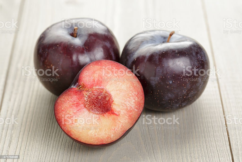 three ripe black plums on wood table stock photo