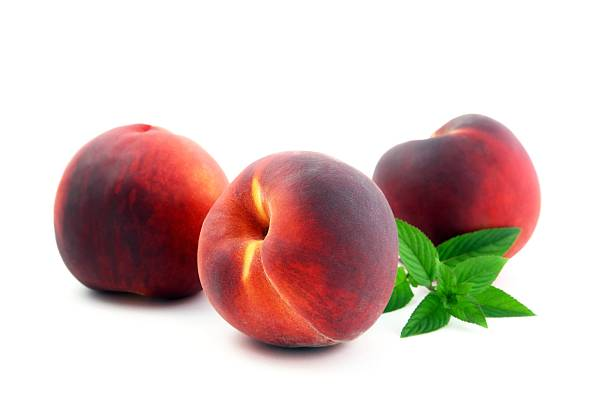 Three Ripe Peaches and Mint Leaves stock photo