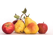 Three ripe yellow skinned pears and red apples, fresh organic beautiful studio shot with stems and green leaves