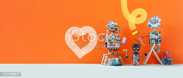 910163152 istock photo Three robots artists designers, orange wall background. One of the cyborgs painted a heart with light paint. copy space 1211563577