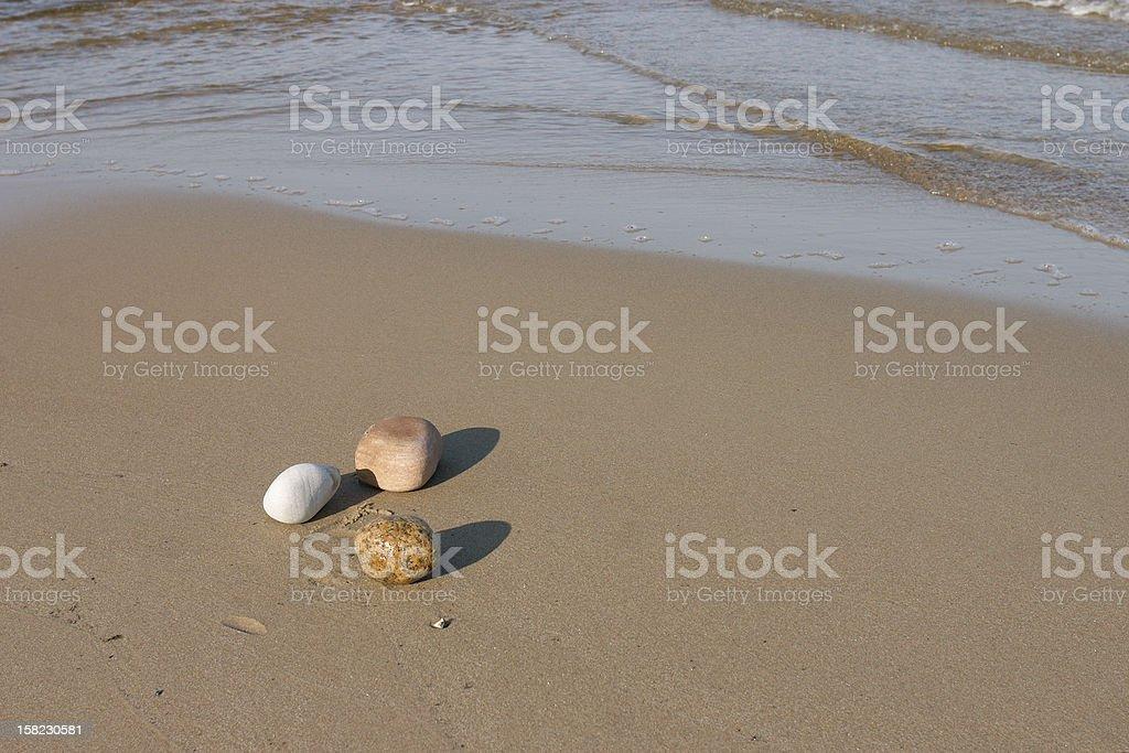 Three rocks at the shoreline inspires tranquility. royalty-free stock photo