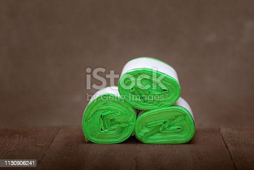 istock Three roll green eco garbage bag end view isolated on brown wooden background. 1130906241