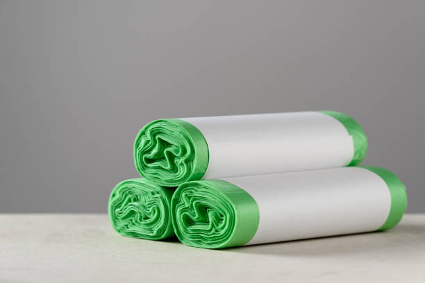 three roll green eco garbage bag with copy space isolated on grey background. - biodegradabile foto e immagini stock