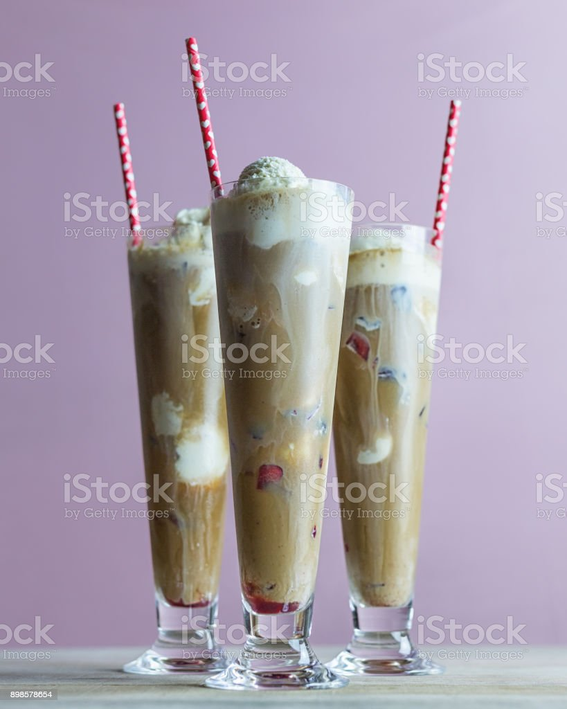 Three root beer floats with vanilla ice cream in tall glasses. stock photo