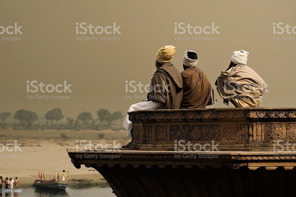 Three sadhus meditating by the Yamuna in Vrindavan stock photo