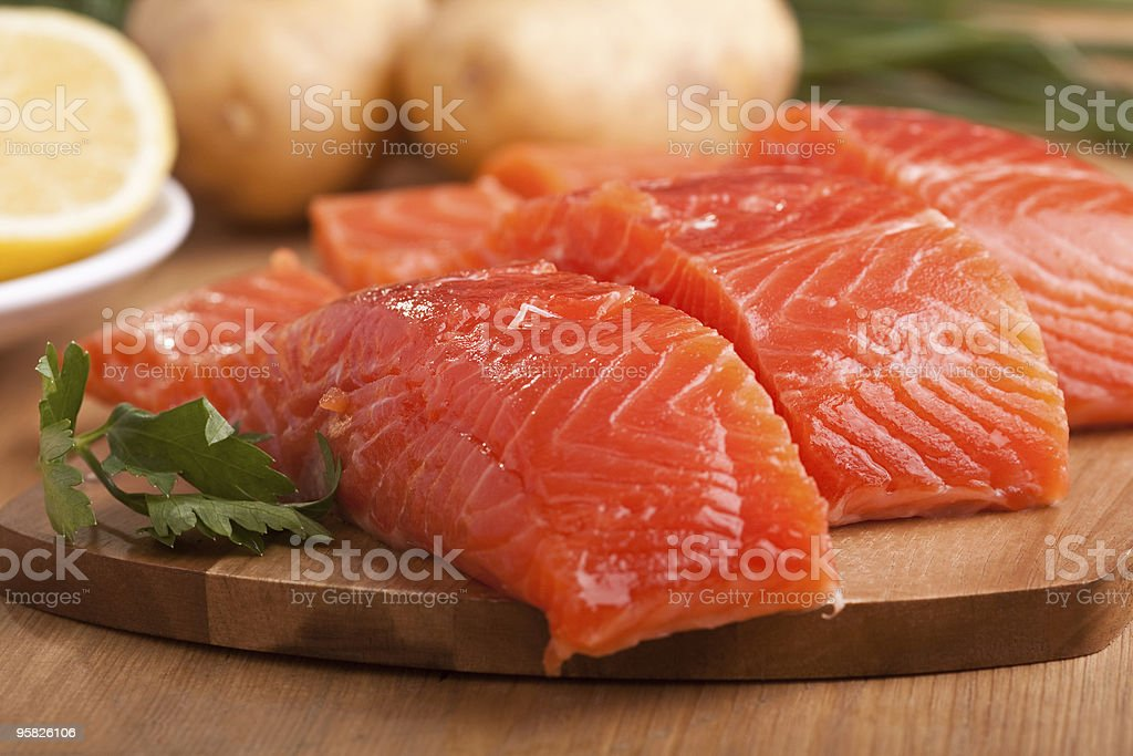 three salmon pieces on a chopping board stock photo