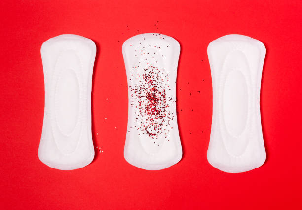 Three sanitary pads on a coral red background. Three sanitary pads on a coral red background. The concept of critical days, menstruation, women's periodic cycle. porous stock pictures, royalty-free photos & images