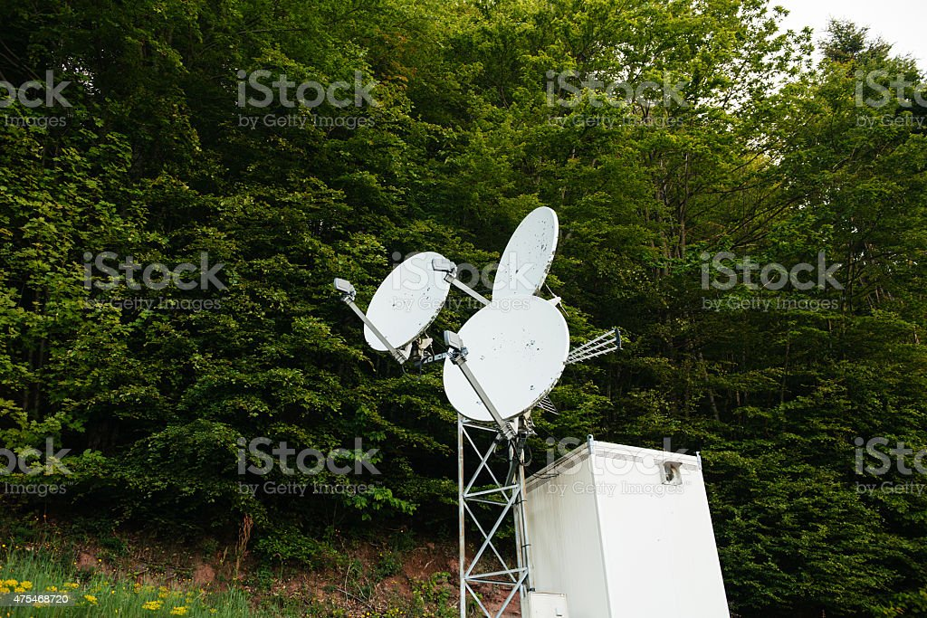 Three satellite dish on a communication tower in forest stock photo