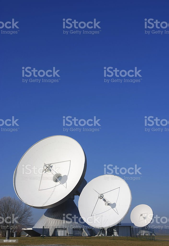 three satellite dishes against clear blue sky  Antenna - Aerial Stock Photo