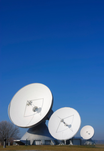 Three Satellite Dishes Against Clear Blue Sky Stock Photo - Download Image Now