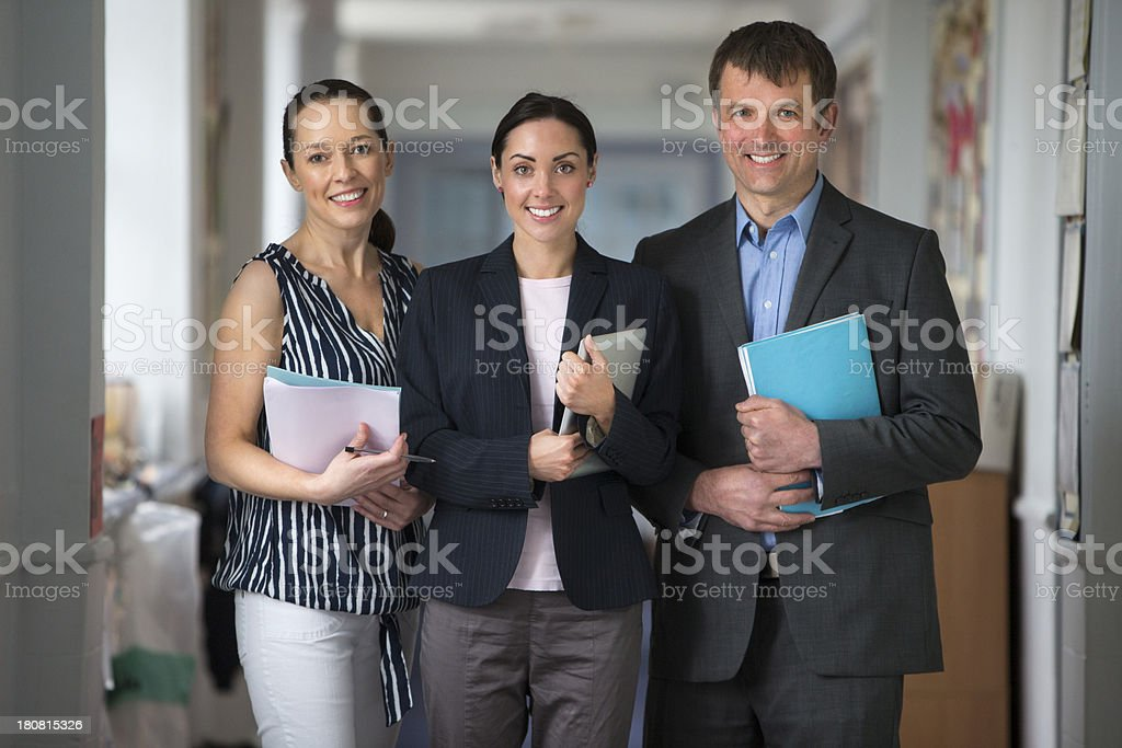 Three School Teachers Holding Paperwork And Smiling royalty-free stock photo