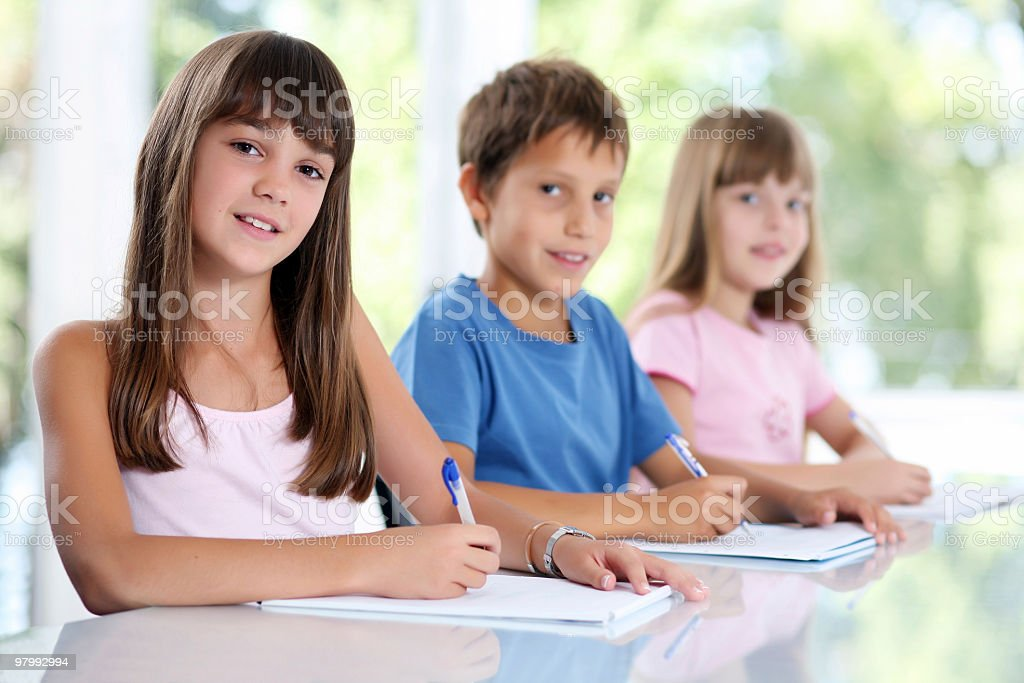 Three schoolchildren sitting in classroom. royalty-free stock photo