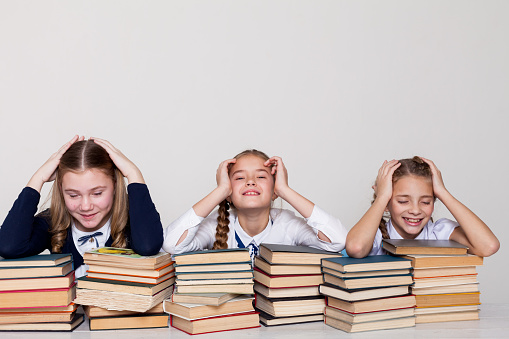istock three schoolgirl girls with books in the library in class at the desk 1220934818