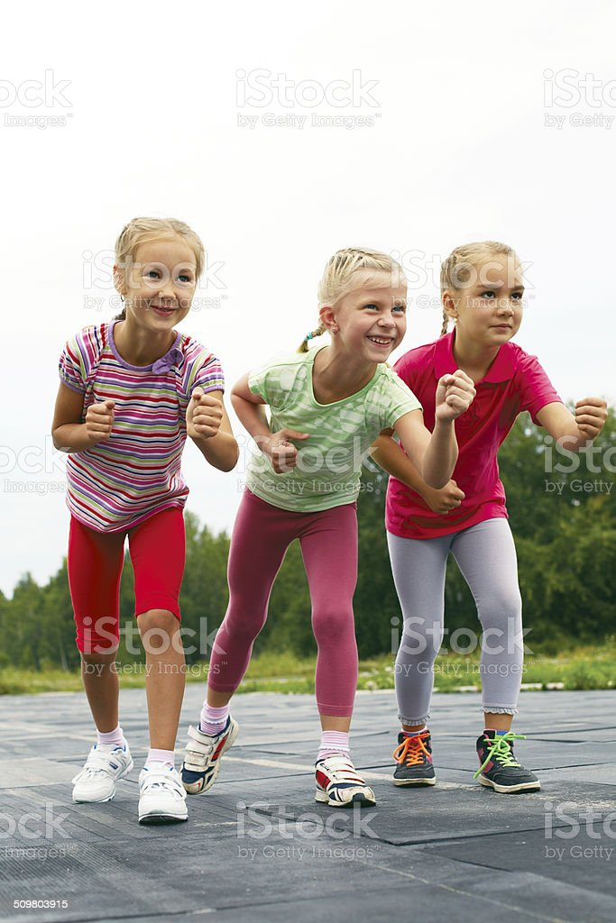 Three schoolgirls are at the start on the treadmill stock photo