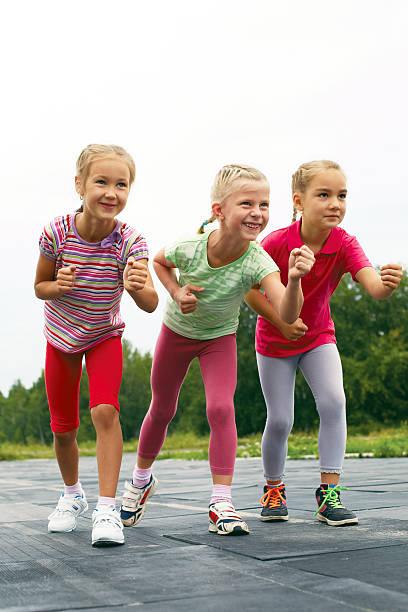 Three schoolgirls are at the start on the treadmill stock photo