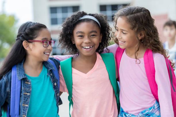three schoolgirls embrace on first day of school - scolara foto e immagini stock