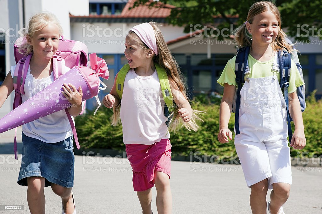 Three schoolgirls walking home from school stock photo