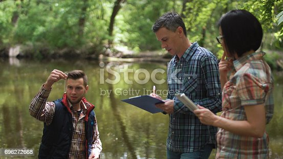 istock Three scientists exploring water in lake 696272668