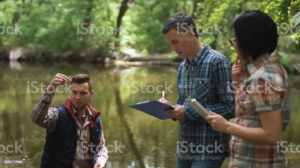 Three scientists exploring water in lake stock photo