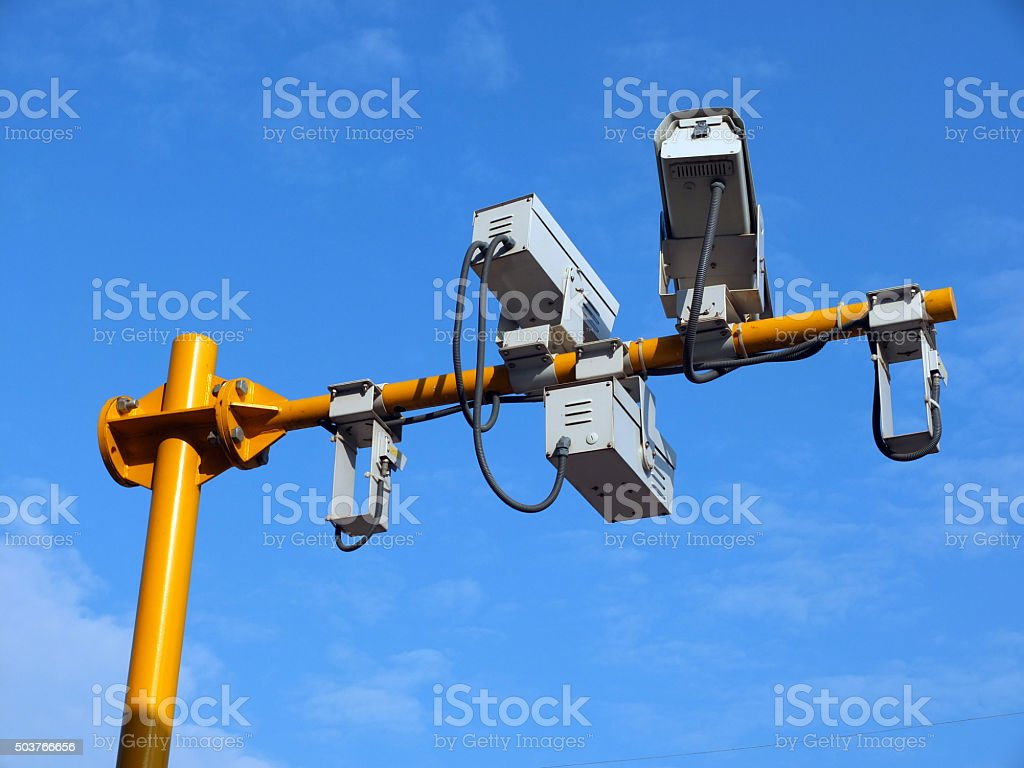 three security cameras on yellow pole with blue sky background stock photo