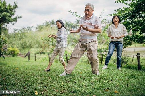 istock Three senior friends exercising in park 1162149782