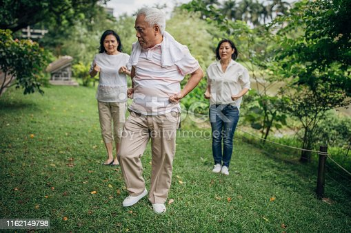 istock Three senior friends exercising in park together 1162149798