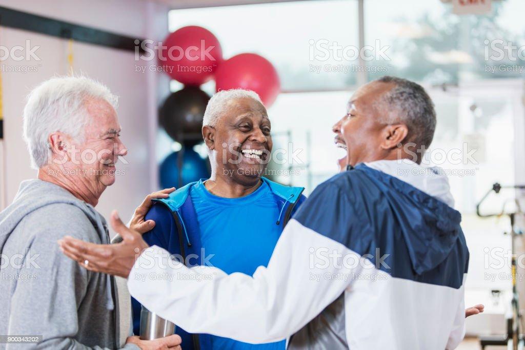 Three senior men hanging out at gym, talking stock photo