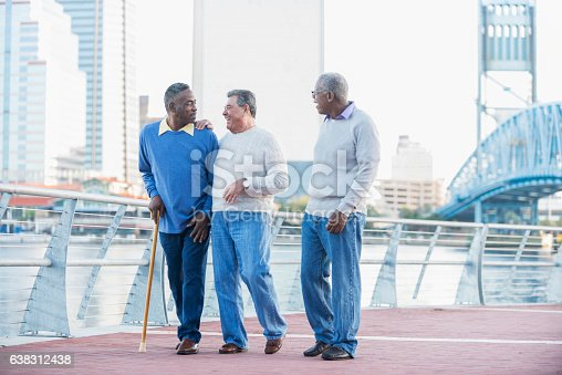 A group of three multi-ethnic senior men walking together along a city waterfront, laughing and talking. The Caucasian man in the middle is in his 80s and his African American friends are in their 60s.