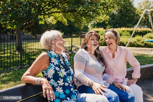 Three senior women are sitting on a park bench laughing in the sunshine.