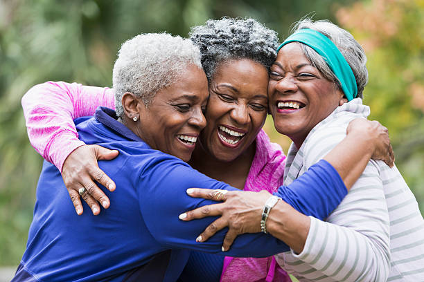 three seniors hugging - reunion stock photos and pictures