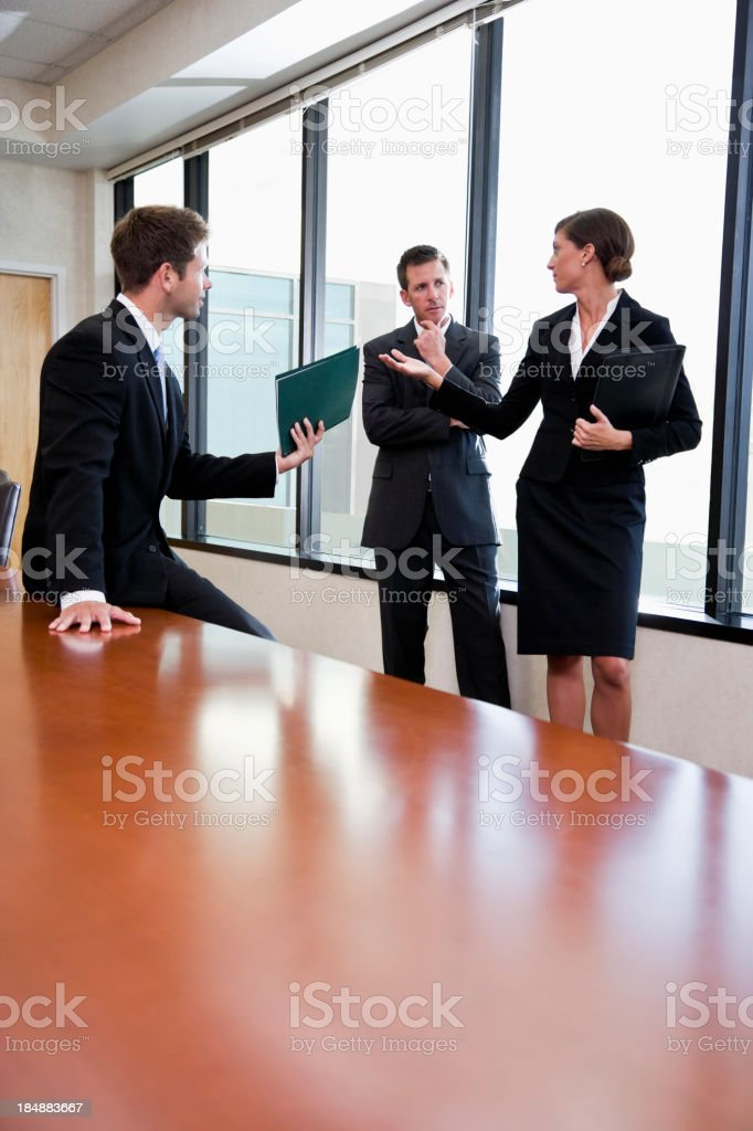 Three serious business people talking in boardroom royalty-free stock photo
