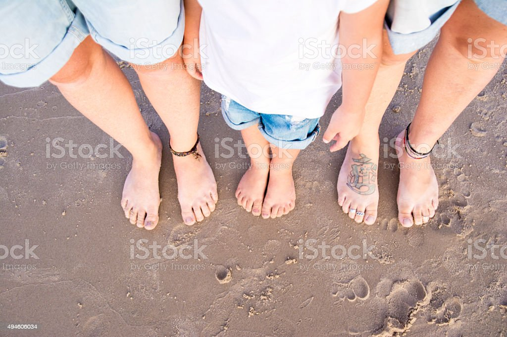 Three sets of feet at the beach stock photo