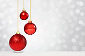 Three sparkly red Christmas ornaments hanging on the left of the image in front of the snowy white defocused  background. Focus is on the baubles, while the background is heavily blurred.