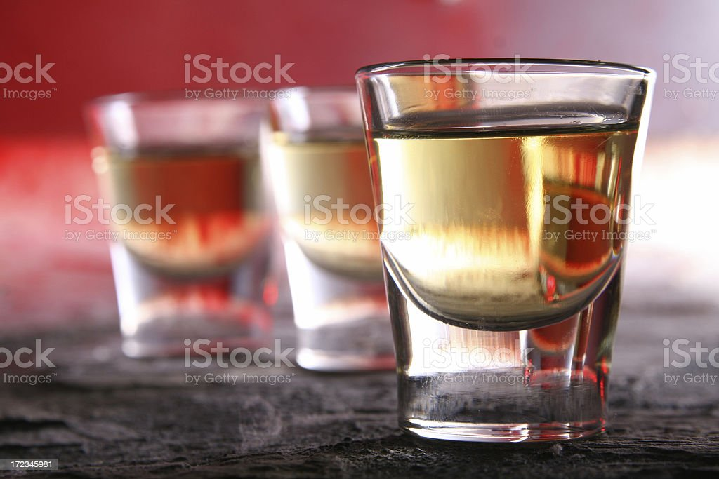 Three shots of alcohol in shot glasses stock photo