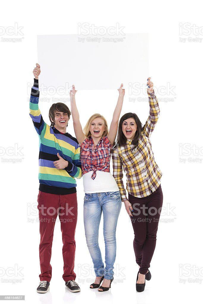 Three shouting young people with banner stock photo