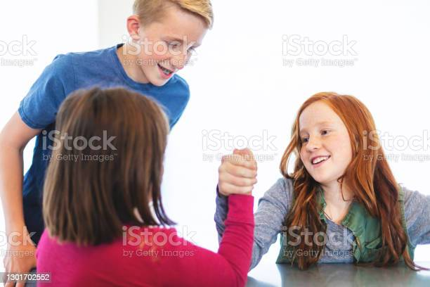 Three Siblings Arm Wrestling Together At Dining Table Photo Series Stock Photo - Download Image Now