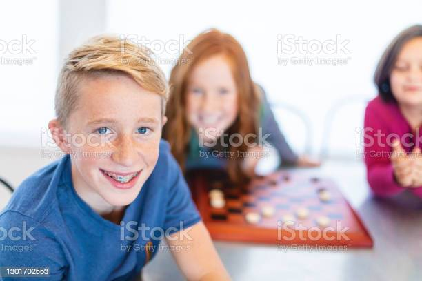 Three Siblings Playing Checkers Together At Dining Table Photo Series Stock Photo - Download Image Now