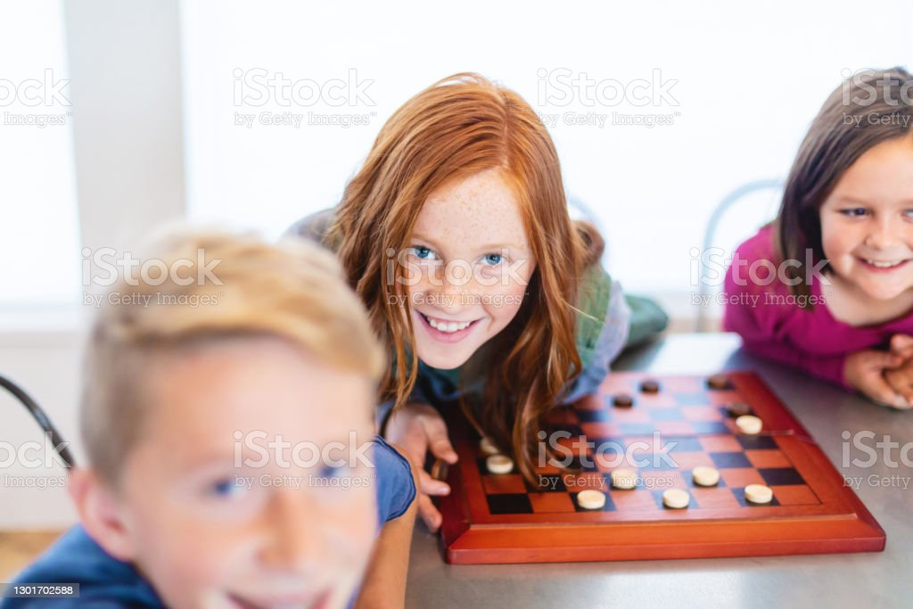 Three Siblings Playing checkers together at Dining Table Photo Series In Western Colorado Three Siblings Playing together at Dining Table Photo Series Matching 4K Video Available (Shot with Canon 5DS 50.6mp photos professionally retouched - Lightroom / Photoshop - original size 5792 x 8688 downsampled as needed for clarity and select focus used for dramatic effect) 10-11 Years Stock Photo