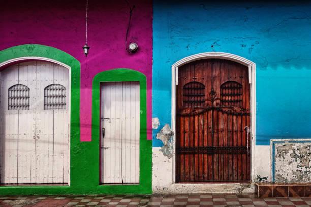 drei side-by-side bunt bemalten türen mit abblätternde farbe und abgenutzte finish in der kolonialstadt leon im norden des landes - nicaragua stock-fotos und bilder
