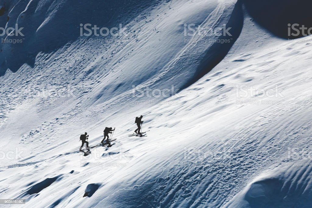Three silhouettes of extreme skiers ascending stock photo