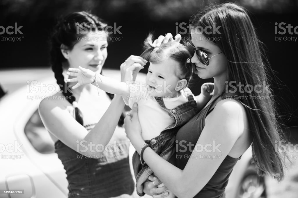 Three sisters in the park. Girls are preparing for photosession and adjusting their hairstyles royalty-free stock photo