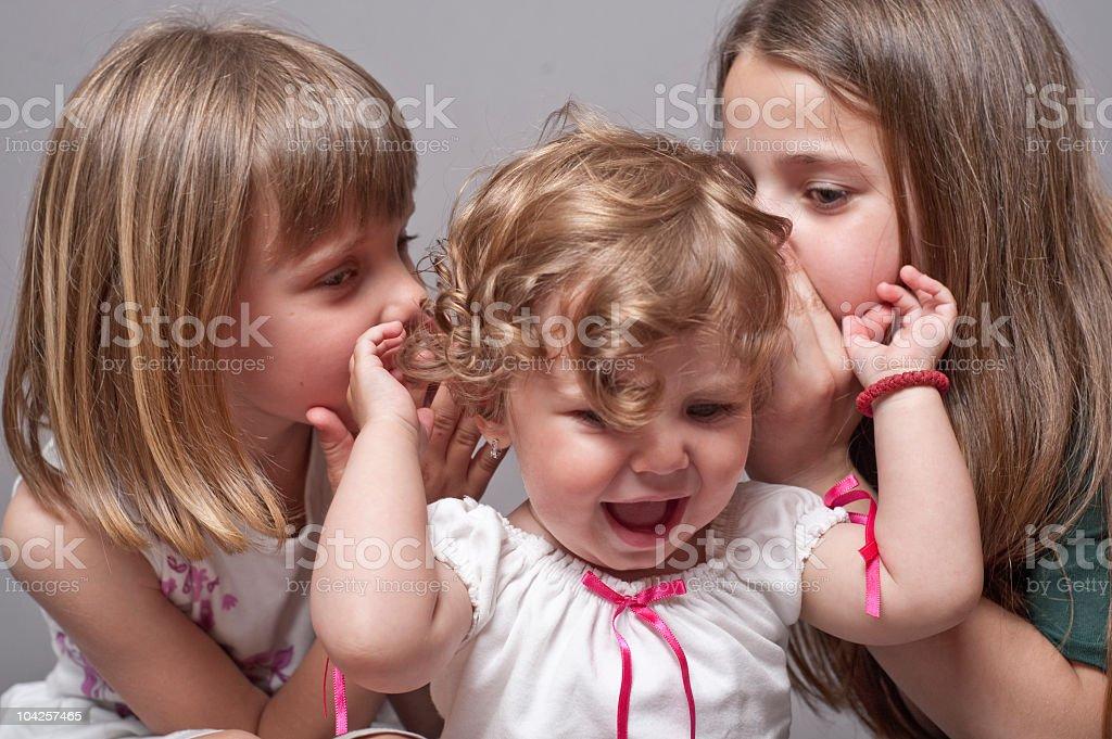 Three sisters whispering stock photo