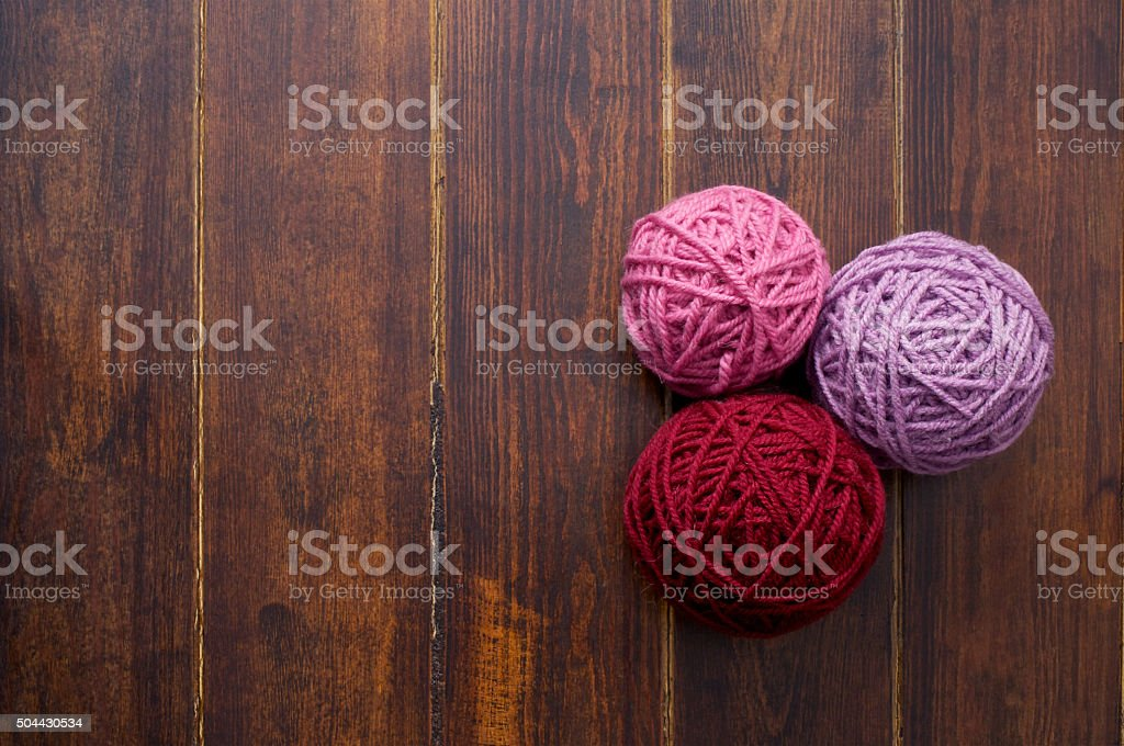 Three skeins in red and pink tones over wooden background stock photo