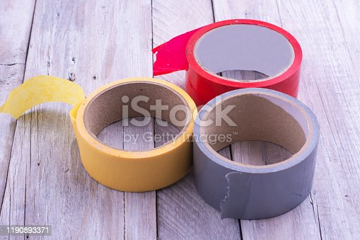 istock Three skeins of multicolor tape on an old wooden table. 1190893371