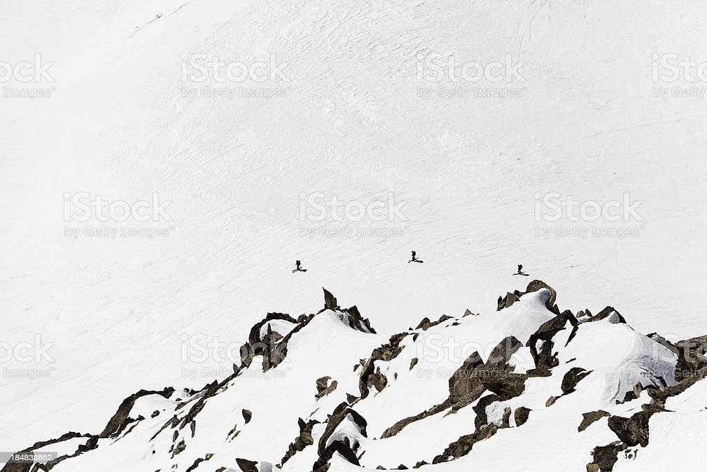 Three Skiers on the Mont Blanc Massif stock photo