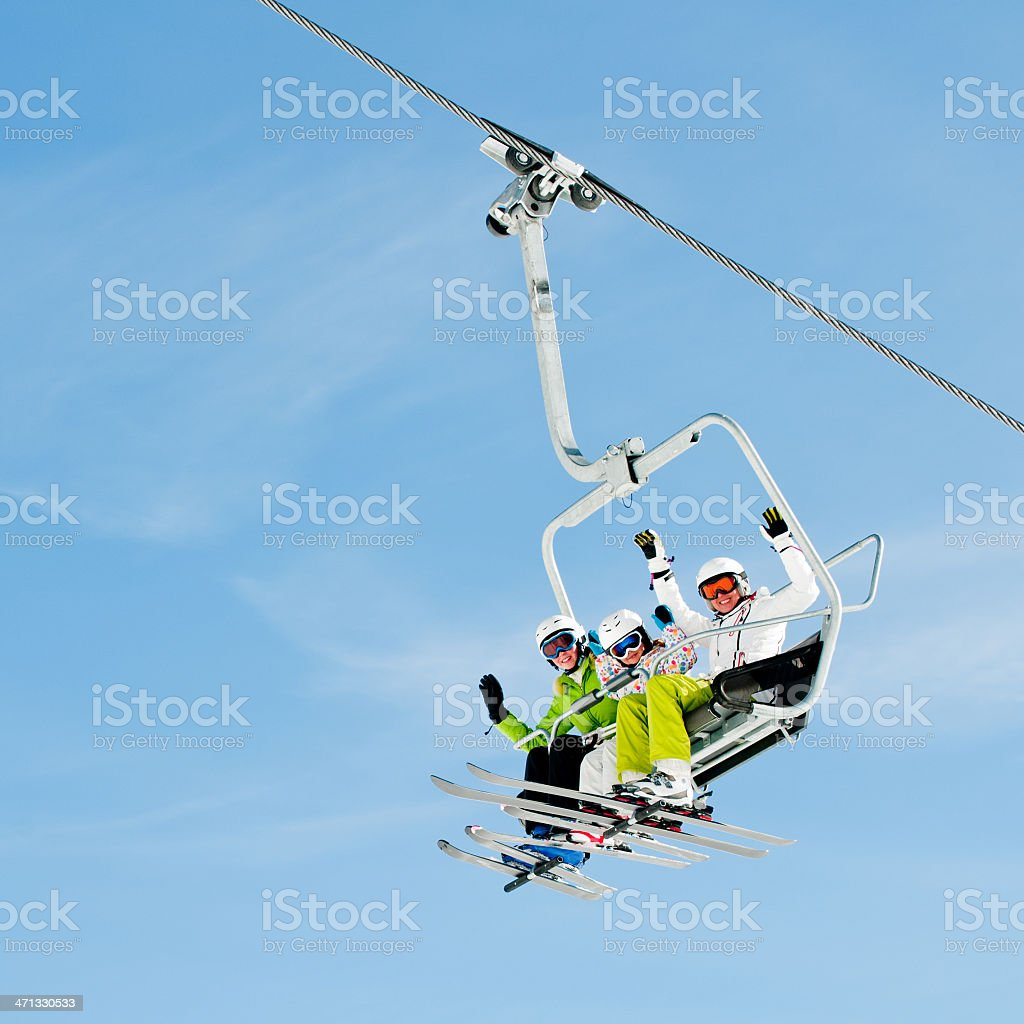 Three skiers riding a ski lift and waving to the camera stock photo