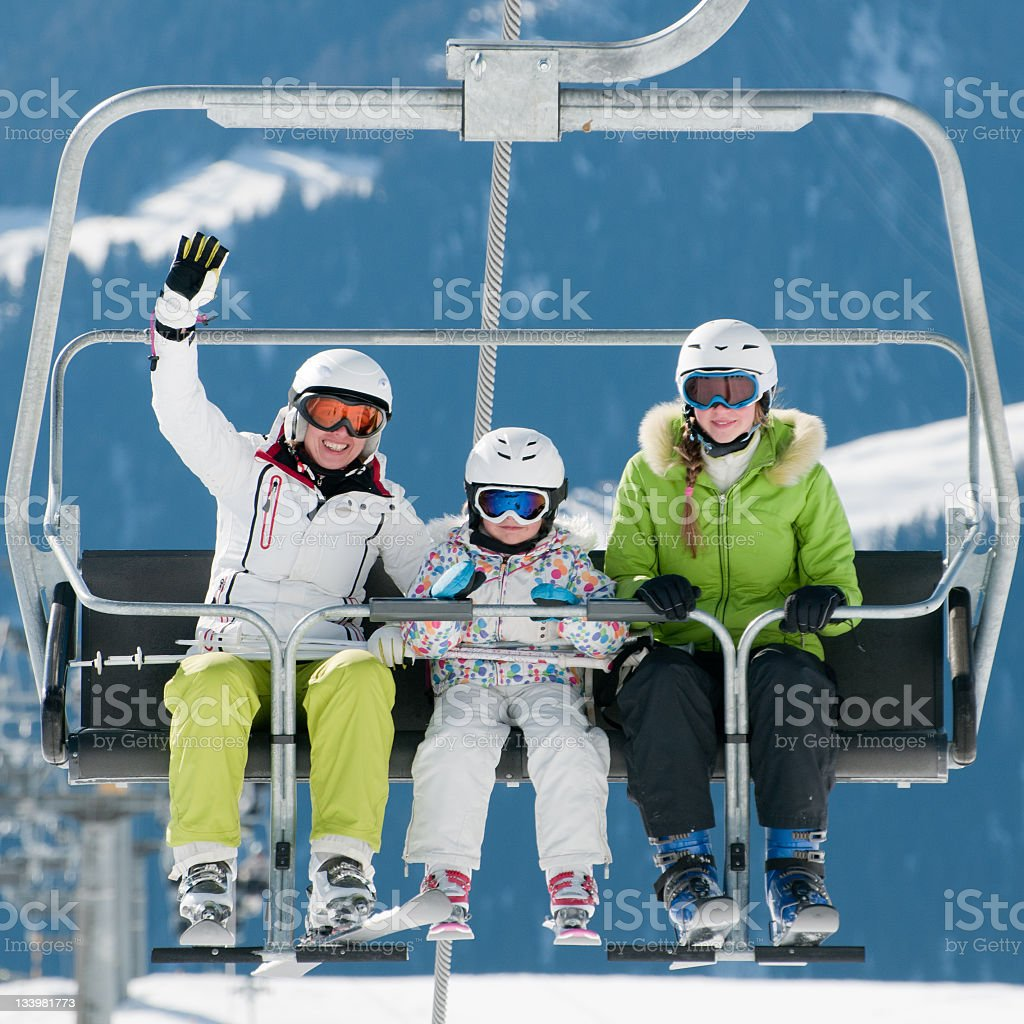 Three skiers riding a ski lift royalty-free stock photo