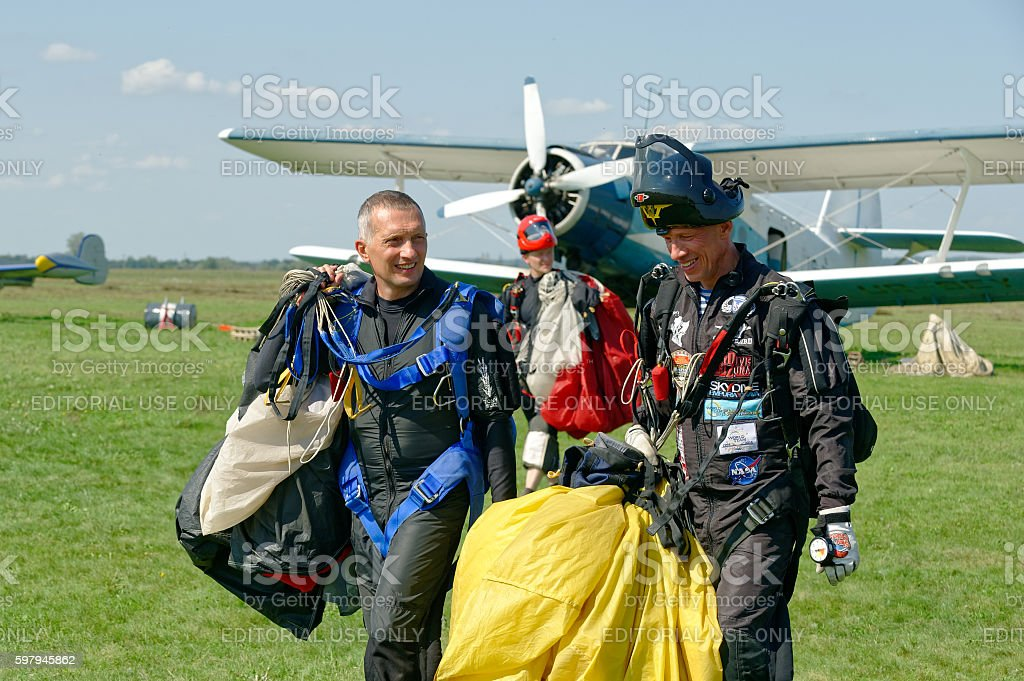 Three  skydivers carries a parachute after landing at the airfield foto royalty-free