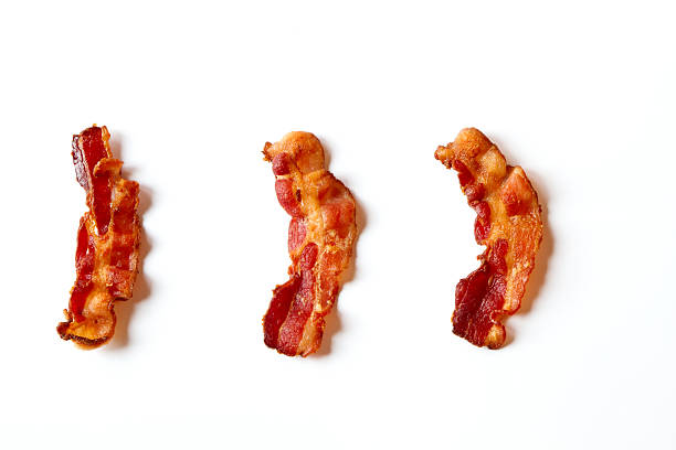 three slices of bacon isolated on a white background - 脆 個照片及圖片檔
