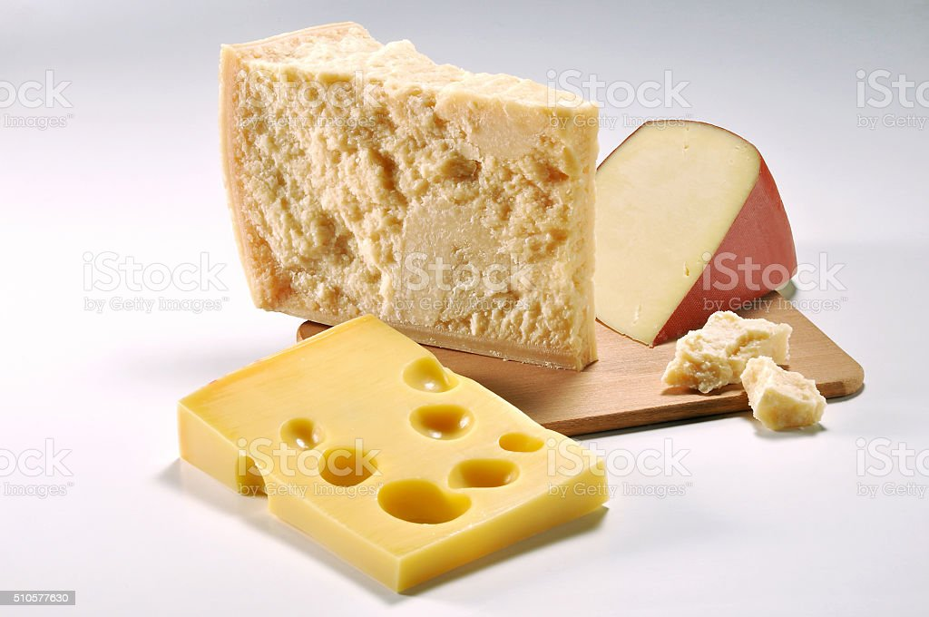 Three slices of Cheese on cutting board stock photo